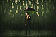 Businessman standing with umbrella in dollar bill rain concept Stock Image