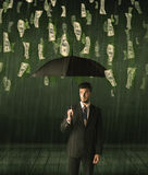 Businessman standing with umbrella in dollar bill rain concept Royalty Free Stock Photography