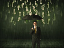 Businessman standing with umbrella in dollar bill rain concept Stock Photos