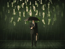 Businessman standing with umbrella in dollar bill rain concept Royalty Free Stock Photos