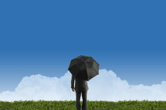 Businessman standing with umbrella on green grass Stock Photography