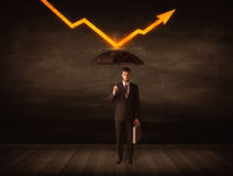 Businessman standing with umbrella keeping orange arrow Stock Photos