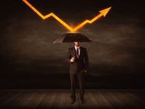 Businessman standing with umbrella keeping orange arrow Royalty Free Stock Photos