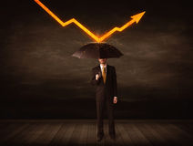 Businessman standing with umbrella keeping orange arrow Stock Photo
