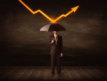 Businessman standing with umbrella keeping orange arrow Royalty Free Stock Photography