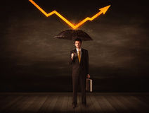 Businessman standing with umbrella keeping orange arrow Royalty Free Stock Photo