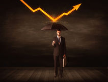 Businessman standing with umbrella keeping orange arrow. Concept on background Stock Photo
