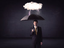 Businessman standing with umbrella and little storm cloud Royalty Free Stock Images