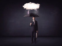 Businessman standing with umbrella and little storm cloud Royalty Free Stock Photos