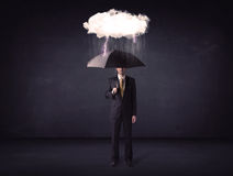 Businessman standing with umbrella and little storm cloud Stock Image