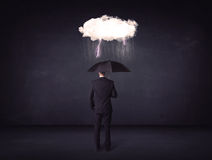Businessman standing with umbrella and little storm cloud Royalty Free Stock Photo