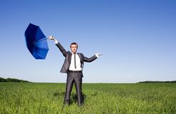Businessman standing with umbrella in the meadow Royalty Free Stock Photo