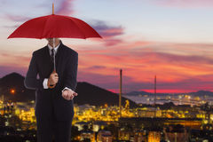 Businessman standing umbrella. Businessman standing in the shade on a harbor backdrop Stock Image
