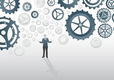 Businessman standing under cogs and wheels Stock Photo