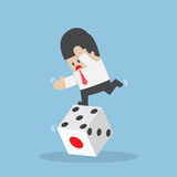Businessman standing on unstable dice. Business risk and luck concept Royalty Free Stock Photo