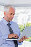 Businessman standing and using laptop. In his office Royalty Free Stock Images