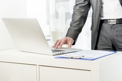 Businessman standing using a laptop Royalty Free Stock Image