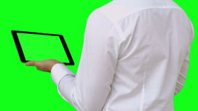 Businessman standing using tablet pc. On green screen background stock video