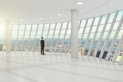 Businessman standing in the white great hall of the business center, and looks towards the city royalty free stock photography