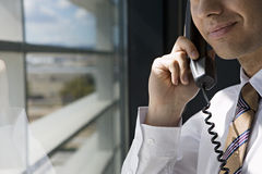 Businessman standing beside window in office, using telephone, smiling, side view, close-up Royalty Free Stock Images