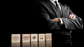 Businessman standing beside wooden blocks with drawings of commu Royalty Free Stock Photos