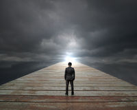 Businessman standing on wooden way face sunlight with cloudy sky Royalty Free Stock Photos