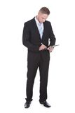 Businessman standing writing on a handheld clipboard Royalty Free Stock Photography