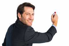 Businessman standing and writing while looking at camera Stock Images