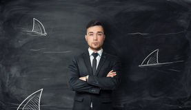 Businessman stands on background with sketches of shark fins. Royalty Free Stock Image