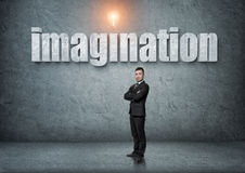 Businessman stands with big 3d 'imagination' word above. Businessman stands with his arms folded with big 3d 'imagination' word above. Ideas and concepts Royalty Free Stock Photo