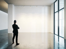 Businessman stands in blank white museum interior with concrete floor. Horizontal Stock Photos
