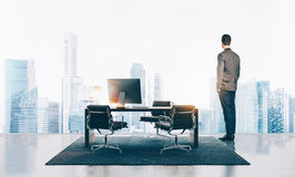 Businessman stands in contemporary office and looking at the city. Horizontal stock image