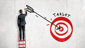 A businessman stands and draws on the wall a big arrow in the center of a red archery target. Business and success. Build your future. Reach your goals stock images