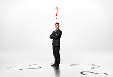 Businessman stands with exclamation mark above him and questions on floor. Businessman stands with folded arms with an exclamation mark above him and question stock image