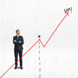Businessman stands with folded arms looking upwards behind big rising diagram, isolated on white background Stock Image