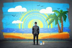 A businessman stands with his back turned and looking at a finished wall picture of exotic isle. royalty free stock images