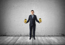 Businessman stands holding pictured bags of money on concrete wall Royalty Free Stock Images