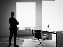 Businessman stands in modern office with empty white canvas. BW Stock Images
