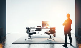 Businessman stands in modern office and looking at horizon. Bokeh effects Stock Images