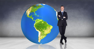 Businessman stands near big earth ball Stock Images