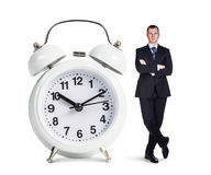 Businessman stands near big white alarm clock Royalty Free Stock Photography