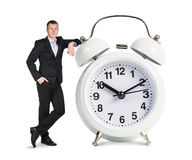 Businessman stands near big white alarm clock Stock Images