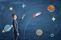 A businessman stands near a blackboard with drawings of planets and points to the rocket. royalty free stock images