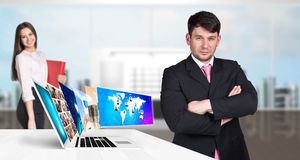 Businessman stands near laptop with many screens. Stock Photos