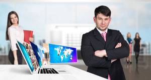Businessman stands near laptop with many screens. Stock Image