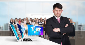 Businessman stands near laptop with many screens. Royalty Free Stock Images