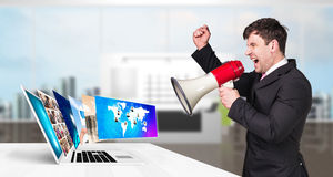 Businessman stands near laptop with many screens. Royalty Free Stock Photo