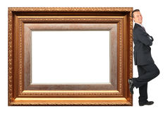 Businessman stands near Picture frame baget. Collage stock photos