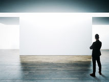 Businessman stands opposite big white wall in museum interior with wooden floor. Horizontal stock photos