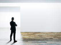 Businessman stands opposite white wall in museum interior with wooden floor Stock Photos
